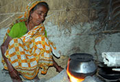 Woman squats next to pot cooking over an open flame, thatched walls in background