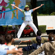 A female instructor on stage leads a large, outdoor exercise class