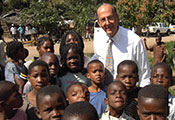 Roger Glass poses outdoors with a group of African children