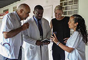 Dr. Bill Pape reviews information on a mobile device with three researchers in a hallway in Haiti