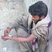 Pakistani man squats on ground against wall while injecting need into forearm