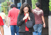 Woman lights cigarette while walking down sidewalk