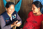 Health worker enters data on mobile device while seated pregnant patient looks on