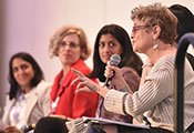 Dr. Michele Barry speaks into a microphone while seated on a dais with four women during a panel discussion at a conference
