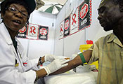 Female health worker performs a blood test on a man, stop AIDS posters on the wall