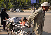 A man and woman push a stretcher holding an injured man through the streets of Chandigarh, India.