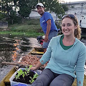 Dr. Leann Andrews seated in small boat on the water next to seedlings in soil.