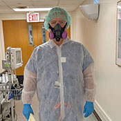Dr. Mark Brady stands in the hallway of a hospital wearing full PPE, including a hair net, half-mask respirator, suit and gloves.