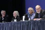 Panel of leaders from across NIH sit at long conference table on stage, some speak into microphones, look pleasant, engaged