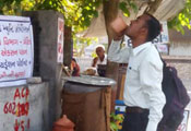 In India, a man drinks from a cup at a public outdoor drinking water station in the shade on a street corner