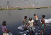 Many men wading in river bank rinsing large clumps of plastic bags, smoking factories in background on opposite bank