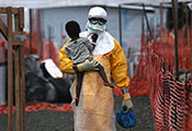 Photo by John Moore/Getty Images, Health worker in personal protective equipment carries a child suspected of having Ebola in treatment center