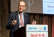 Dr. Roger I. Glass speaks from a podium labeled CUGH 2018, slide projected in the background