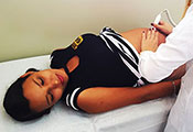 Pregnant teenage girl lies on her back in an exam room while a medical worker with her back to the camera examines her belly