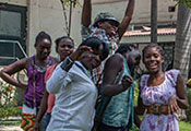 Group of teenagers in outdoor courtyard in Haiti pose for camera