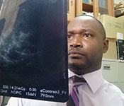 Dr. Mubuuke Gonzaga holds up and examines an x-ray.