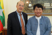 Fogarty Director Dr Roger I Glass stands with Burma's health minister Dr Pe Thet Khin, Burmese flag in background