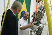 Dr Francis Collins observes as researchers demonstrates  movement of a large metal robot, Brazilian flag in background