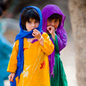 Two young Pakistani girls stand together looking at camera wearing brightly colored outfits and headscarves