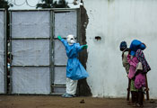 Photo by Morgana Wingard, courtesy of USAID, Healthcare worker outside Ebola clinic in full protective gear holds gate closed, warns away approaching people