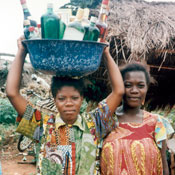 � 1996 Sara A. Holtz, Courtesy of Photoshare, 2 African women outdoors, one balances tub full of alcohol bottles on her head