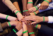 Hands join in the middle of a huddle pictured from above, all wearing bright green Fogarty wristbands