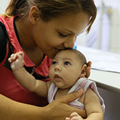 Photo by Harold Ruiz/PAHO-WHO. In Brazil, a mother kisses a baby, who has a smaller than usual head