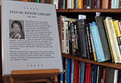 Plaque reading Ellis McKenzie Library sits on easel with shelves full of books