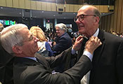 Dr Tony Fauci straightens Dr Roger Glass's bowtie in the audience of the auditorium during the Fogarty 50th anniversary symposium