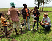 Two global health students collect data on mobile devices from community members, rural farmland in the background.