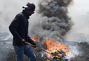 Man prods pile of burning electronic waste with a stick. Fire gives off a large cloud of thick, dark smoke.