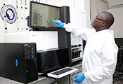 Photo courtesy of Dr. Christian Happi. Dr. Happi works in a lab on a large touch screen monitor.