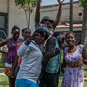 Photo courtesy of GHESKIO. Group of teenagers in outdoor courtyard in Haiti pose for camera.