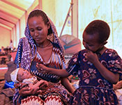 Photo by UNICEF Ethiopia/2021/Nahom Tesfaye. Woman holds a newborn baby, older child seated next to her on a cot, in a large tent clinic.