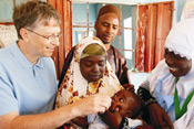 Bill Gates administers polio vaccine to baby, held by mother, another man and woman look on