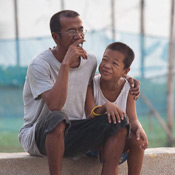 Man smoking cigarette seated outside, arm around young boy