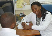 Dr Akwi Asombang in white coat with stethoscope seated at desk takes note on pad while speaking with a seated patient