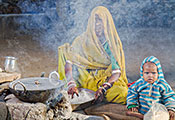(c) 2014 Louis Kleynhans, Courtesy of Photoshare. Woman seated next to smoking stone cookstove, young child seated next to her.