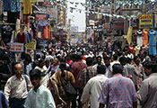 © 2003 Vijay Sureshkumar, Courtesy of Photoshare. City street very crowded with pedestrians, tall buildings with signs and merchandise line the street.