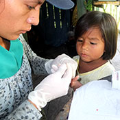 Medical worker administers fingerstick blood test on young girl in Peru