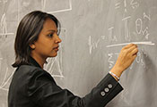 A scientists intently works a complex math problem with chalk on a blackboard