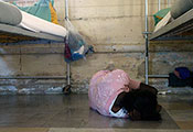 Photo by Torsten Blackwood / AFP / Getty Images. Person lies on floor curled into ball facing away from camera next to metal bed frames in an institution.