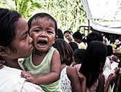 © 2012 Jundio Salvador, Courtesy of Photoshare. Crying child held while waiting in long line outdoors in the Philippines.