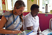 Photo by Sarah Graham. Dr. Lisa Bebell works with research nurse Honest Twinomujuni to record data in a clinic.