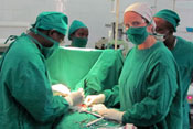 Dr Robin Petroze in green hospital scrubs and mask during a surgery with one additional surgeon, two workers in background