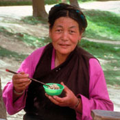 Asian woman eats using chopsticks seated at an outdoor table