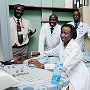 Medical student works with a patient, teacher and other students observe