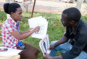 A female researcher in Uganda, seated across from a male research subject, points to low-literacy materials