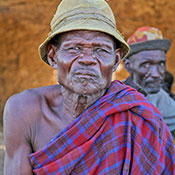 Elderly African man seated outside looks directly at camera
