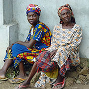 Two older women in Nigeria seated outdoors on a pile of rocks